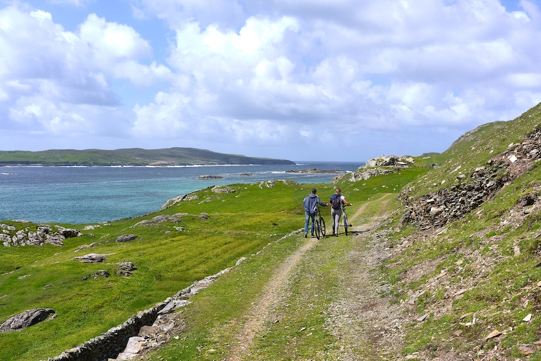 Cyclers along the Wild Atlantic Way, on the sunny shores of Inishbofin Island.